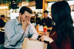 Den ledsna bilden av manbeläggning hastar framsidan med handen Han doesn` t förstår vad hans flickvän talar om Men henne royaltyfri fotografi