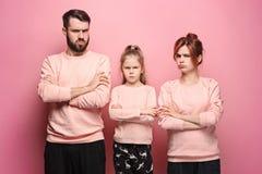 Den ledsna familjen på rosa färger royaltyfria foton