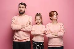 Den ledsna familjen på rosa färger royaltyfria bilder