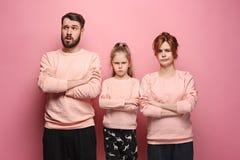 Den ledsna familjen på rosa färger arkivbild