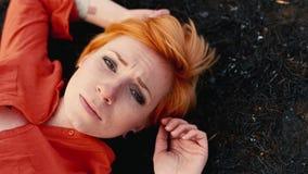 Den ledsna flickan med rött hår som ligger på den svarta jorden som stirrar SAD på himlen Begrepp: behovshjälp, ensamhet stock video