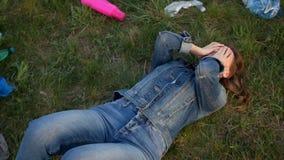 Den ledsna flickan som ligger täcka hans ögon på avskrädet, fyllde gräs - plast- föroreningbegrepp r stock video