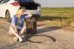 Den ledsna flickan vars chaufför har kört ut ur bensin i en bil på en lantlig väg, sitter väntande på hjälp med en bränslekaniste royaltyfri foto
