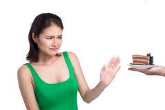 Den ledsna framsidan av den asiatiska unga kvinnan gillar inte kakan isolerad på vit Arkivfoton