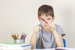 Den ledsna ilskna pojken har svårigheter som gör läxa royaltyfri foto