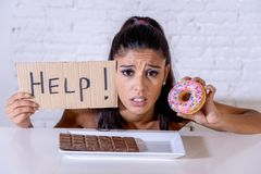 Den ledsna kvinnan bantar på rymma en teckenhjälp som motstår frestelse att äta choklad och donuts royaltyfria foton