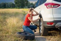 Den ledsna kvinnan fick förvirrad om att ändra det plana gummihjulet i fältet Arkivbild