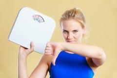 Den ledsna kvinnan med tummen för viktvinst undertecknar ner Royaltyfri Foto