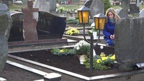 Den ledsna kvinnan satte stearinljuset på grav av den älskade faderbrodern i kyrkogård 4K lager videofilmer