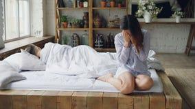 Den ledsna kvinnan sitter på säng och gråt efter kamp med hennes pojkvän, medan han ligger i säng med hans baksida till henne arkivfilmer