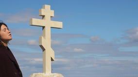 Den ledsna kvinnan som bara står nära kors efter begravning, smärtar på framsidan som ber till guden stock video