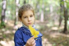 Den ledsna lilla caucasian flickan rymmer bladet och ser arkivbild
