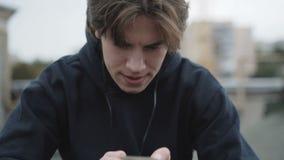 Den ledsna mannen använder smartphonen och hörlurar på ett gatatak arkivfilmer