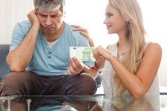 Den ledsna mannen ger 100 euro till guldgrävareblondinkvinnan Fotografering för Bildbyråer