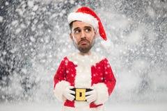 Den ledsna mannen i den Santa Claus dräkten över jul snöar Arkivfoton