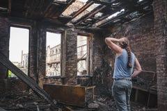 Den ledsna mannen rymmer hans huvud vid handen och skrik i utbränt hus efter katastrofen, följder av brand royaltyfria foton