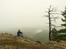 Den ledsna mannen sitter på maximumet av sandsten vaggar och hålla ögonen på över den dimmiga och dimmiga morgondalen Royaltyfria Bilder