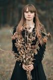 Den ledsna, olyckliga allvarliga härliga flickan med långt hår som rymmer en bukett av den torkade hösten, blommar Bild i mörka f royaltyfria bilder
