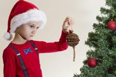Den ledsna pojken i jultomten cap att se xmas-leksaken nära julgranen Arkivfoto