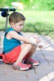 Den ledsna pojken med den brutna armen sitter på sparkcykeln Royaltyfria Bilder