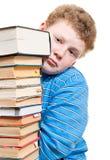 Den ledsna pojken ser ut en hög av bokar bakifrån Arkivfoton