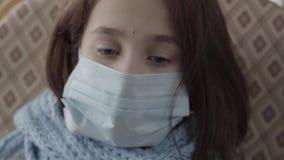 Den ledsna sjuka flickan som sitter i fåtöljen med en steril maskering på hennes framsida som ner hemma ser Begrepp av ett sjukt  stock video