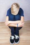 Den ledsna tonåringen sitter på ett golv i rummet Royaltyfria Bilder