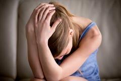 Den ledsna tonåringen som gråter det ensamma hållande huvudet i händer som känner sig trycker ned Fotografering för Bildbyråer