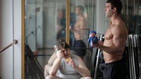 Den ledsna trötta feta mannen håller ögonen på hans idrotts- med- utbildningsarmmuskler med hantlar stock video