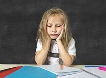 Den ledsna trötta gulliga blonda yngre skolflickan i spänningen som arbetar göra läxa, borrade förkrossat Arkivbild