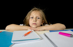 Den ledsna trötta gulliga blonda yngre skolflickan i spänningen som arbetar göra läxa, borrade förkrossat Arkivfoto