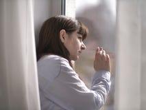 Den ledsna unga brunettkvinnan ser ut fönstret med hennes hand på exponeringsglaset royaltyfri fotografi