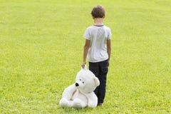Den ledsna unga pojken rymmer en nallebjörn och anseende på ängen Barn som ner ser tillbaka sikt Sorgsenhet skräck Royaltyfri Foto