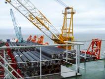 Den lekmanna- pråm för däck Rör och lyftande kranar på skeppet Utrustning för att lägga en rörledning på havsbottnen Royaltyfria Bilder