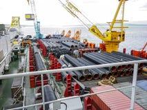 Den lekmanna- pråm för däck Rör och lyftande kranar på skeppet Utrustning för att lägga en rörledning på havsbottnen royaltyfri fotografi