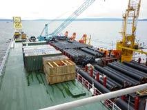 Den lekmanna- pråm för däck Rör och lyftande kranar på skeppet Utrustning för att lägga en rörledning på havsbottnen Arkivbild