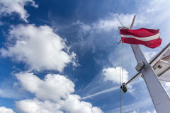 Den lettiska flaggan på skeppmasten med stor stor vit fördunklar royaltyfri fotografi