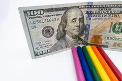 Den LGBT- och Gay Pride regnbågen färgade blyertspennor med en räkning $100 mot en vit bakgrund Jämställdhet- och mångfaldbegrepp fotografering för bildbyråer