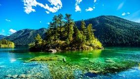 Den lilla ön i mitt av det kristallklara vattnet av paviljong sjön i den provinsiella marmorkanjonen parkerar, British Columbia Arkivfoton