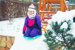 Den lilla aktiva lyckliga flickan bygger is och snökullen med skyffeln Royaltyfria Bilder