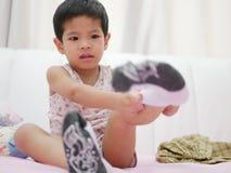 Den lilla asiatet behandla som ett barn att vara grinig, medan hon försöker till pålagda sockor royaltyfria foton