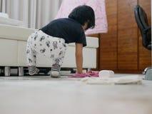 Den lilla asiatet behandla som ett barn flickan som gör ren hennes egen röra, kropppulver, på husgolvet arkivbild