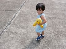Den lilla asiatet behandla som ett barn flickan som rymmer hennes favorit- docka, medan lära att gå vid henne fotografering för bildbyråer