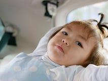 Den lilla asiatet behandla som ett barn flickan som sträcker i en bil under en lång tur - behandla som ett barn sträckning royaltyfria foton