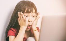 Den lilla asiatiska flickan är chock med vad hon ser på internet Royaltyfri Foto