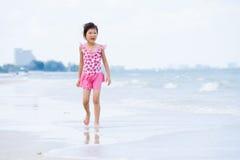 Den lilla asiatiska flickan går på stranden Arkivfoton