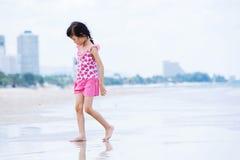 Den lilla asiatiska flickan går på stranden Arkivbilder