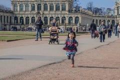 Den lilla asiatiska flickan kör längs banan i Dresden Zwinger, tysk Royaltyfri Bild