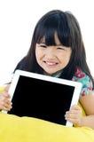 Den lilla asiatiska flickan ler med minnestavladatoren Royaltyfri Bild