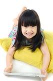 Den lilla asiatiska flickan ler med minnestavladatoren Arkivfoto